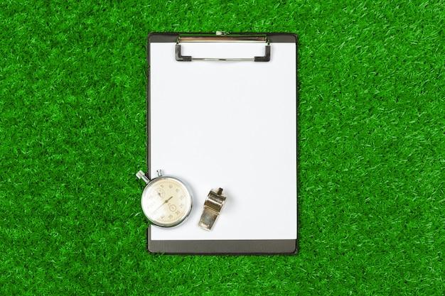 Blatt papier und sportausrüstung auf grasnahaufnahme