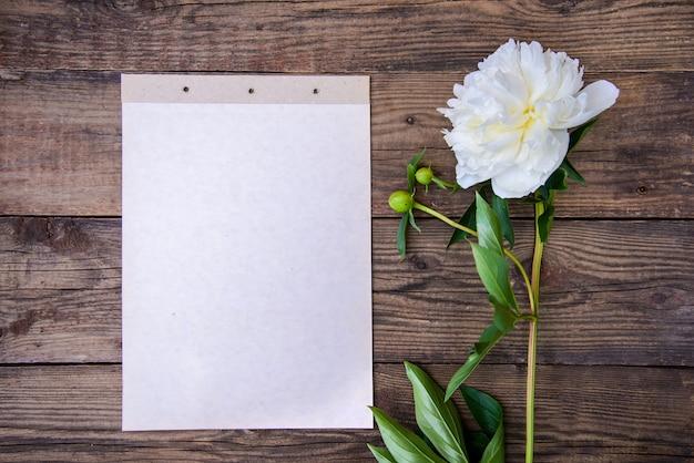 Blatt papier und weiße pfingstrose auf hölzernem hintergrund
