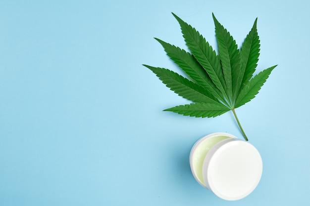 Blatt von cannabis und plastikverpackung oder glas mit kopienraum mit bio-creme enthalten hanföl auf dem blauen hintergrund. herstellung von kosmetikprodukten für die hautpflege.