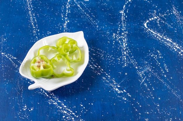 Blattförmiger teller mit grünen paprikaringen auf marmoroberfläche