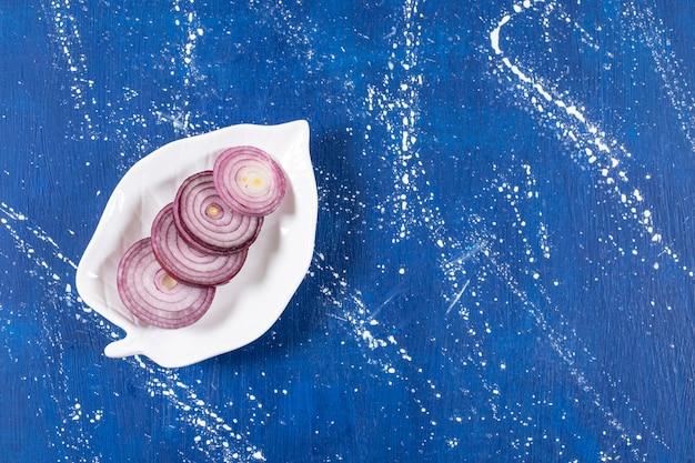 Blattförmiger teller mit violetten zwiebelringen auf marmoroberfläche