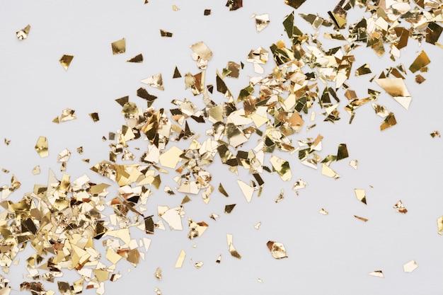 Blattgold-konfetti auf weißem hintergrund. diagonal ausgebreiteter glitzerhintergrund.
