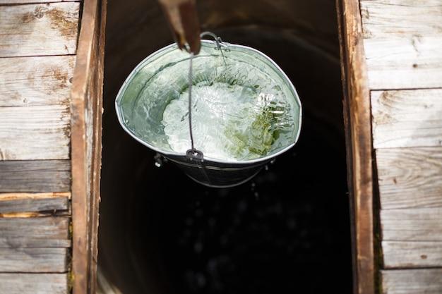Blau bockte im wasserbrunnen. ein wasserbrunnen mit einem alten eiseneimer
