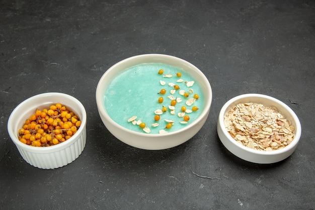 Blau gefrorenes dessert der vorderansicht mit rohem müsli auf dunklem tischcremeeisfrühstück