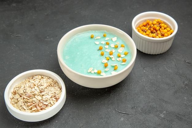 Blau gefrorenes dessert der vorderansicht mit rohem müsli auf eiscremefrühstück des dunklen bodens