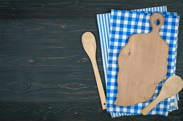 Blau karierte tischdecke und holzgeräte zum kochen und backen. mit kopierplatz. horizontal.