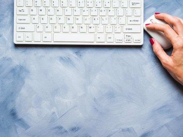 Blau mit der hand und der tastatur der frau