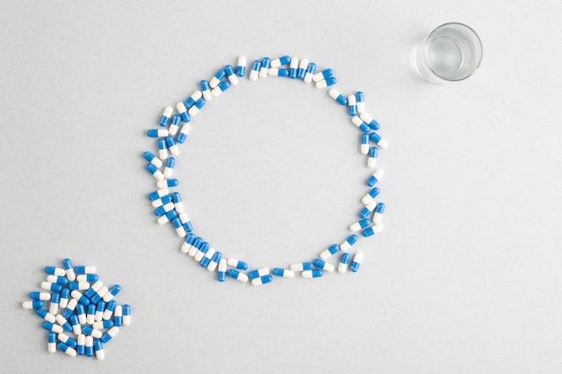 Blau-weiße pillen bilden einen großen kreis über weißem hintergrund mit einem glas wasser und einem stapel kapseln oben rechts und unten links