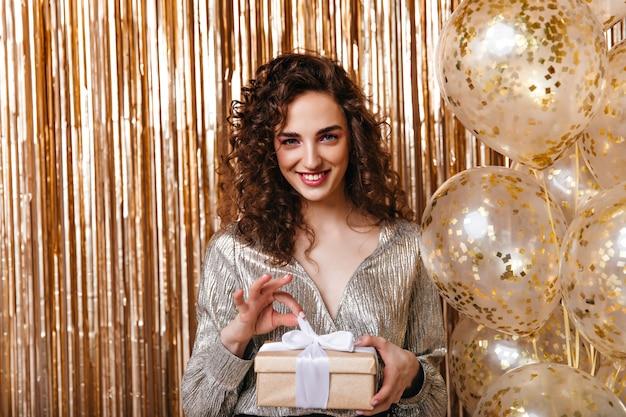 Blauäugige dame in der glänzenden spitze, die geschenk auf goldenem hintergrund hält