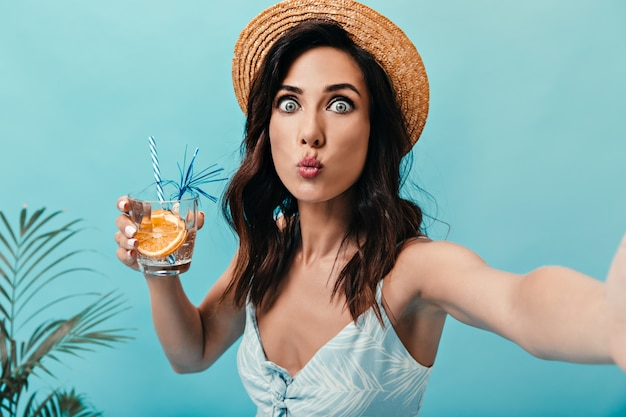 Blauäugige dame pfeift, macht selfie und hält ein glas wasser mit orange