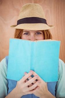 Blauäugige hippie-frau, die einen trilby trägt und über der oberseite eines buches schaut