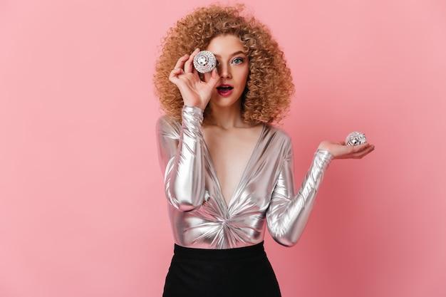 Blauäugige lockige blonde frau gekleidet in glänzendem oberteil, das kamera betrachtet und kleine discokugeln auf rosa raum hält.