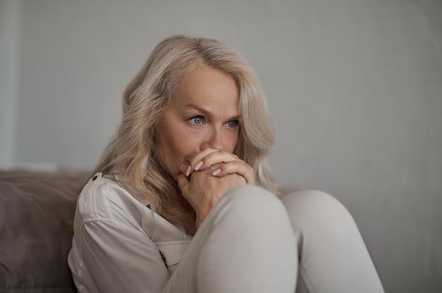Blauäugige reife kaukasische frau mit lockeren blonden haaren, die ihre gefalteten fäuste an ihre lippen drückt