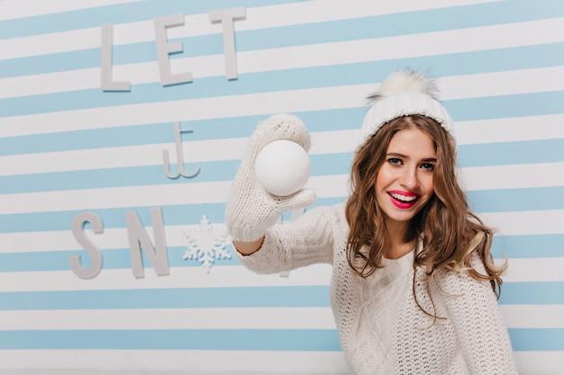 Blauäugige russische schönheit im winter strickte kleidung, die schneeball in ihrer hand hält und lächelt, posierend für nahaufnahme weibliches porträt