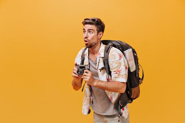Blauäugiger überraschter mann in sommerlichem lichtoutfit und sonnenbrille posiert mit rucksack und kamera an isolierter orangefarbener wand