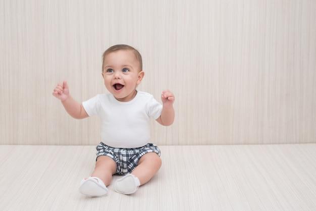 Blauäugiges baby auf weißem hölzernem hintergrund