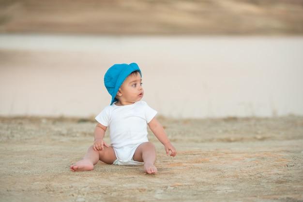 Blauäugiges baby mit dem blauen hut, der auf dem sandboden sitzt