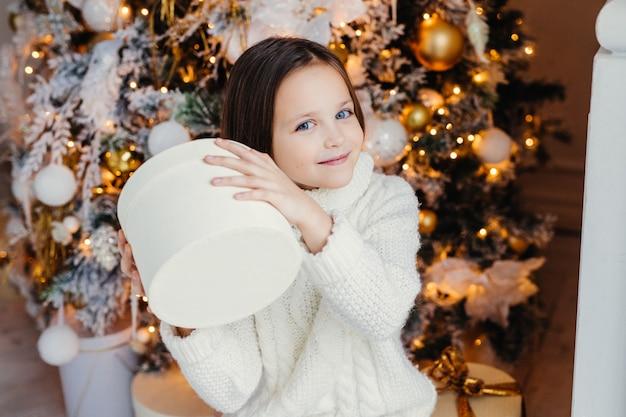 Blauäugiges hübsches kleines kind hält geschenkschachtel, fragt sich, was drin ist, steht in der nähe von neujahr oder weihnachtsbaum, bekommt überraschung von den eltern.