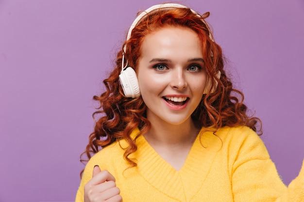 Blauäugiges mädchen im gelben pullover hört musik mit kopfhörern und macht selfies