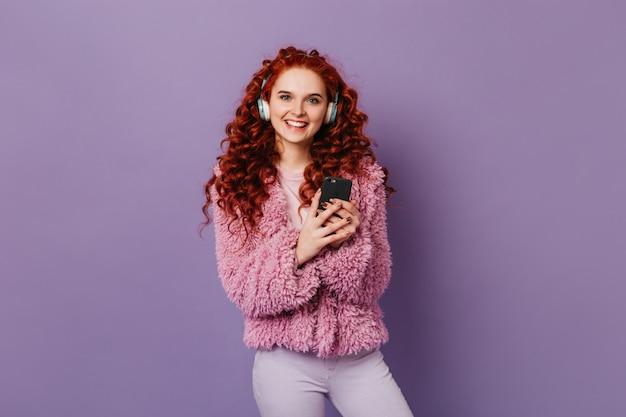 Blauäugiges süßes mädchen betrachtet kamera auf lila raum mit lächeln. lockige rothaarige frau in der rosa jacke, die in den kopfhörern mit telefon in ihren händen aufwirft.