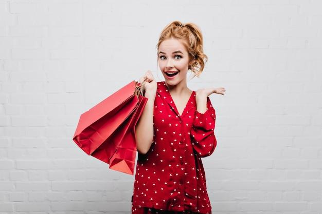 Blauäugiges überraschtes mädchen in baumwollroter nachtwäsche, die mit lächeln auf weißer wand aufwirft wunderbare dame im pyjama, die spaß am geburtstagmorgen hat und geschenktüte hält.