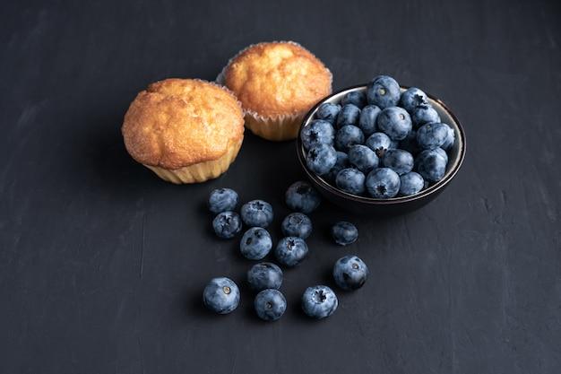 Blaubeer-antioxidans-bio-superfood in keramikschale und süßem muffin konzept für gesunde ernährung und diäternährung