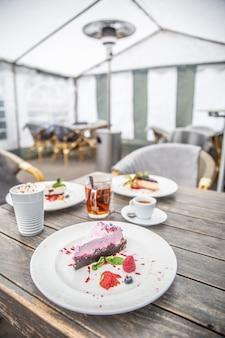 Blaubeer-käsekuchen mit frischen himbeeren auf einem café-tisch mit verschiedenen kaffeesorten und anderen kuchensorten.
