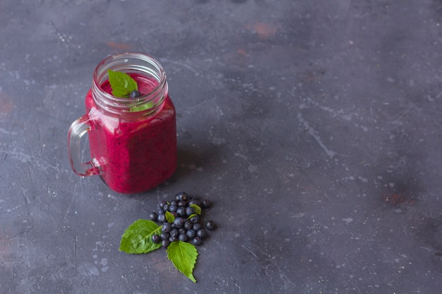 Blaubeer-smoothie im einmachglasbecher mit minze und einigen frischen beeren. das konzept der richtigen ernährung und gesunden ernährung. bio- und vegetarisches getränk. schließen sie, kopieren sie platz für text