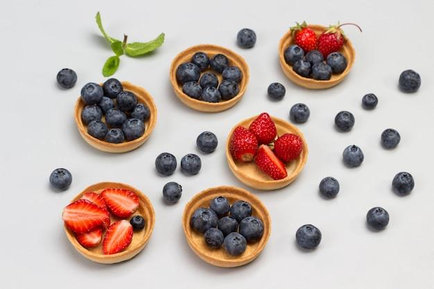Blaubeer- und erdbeertörtchen auf dem tisch