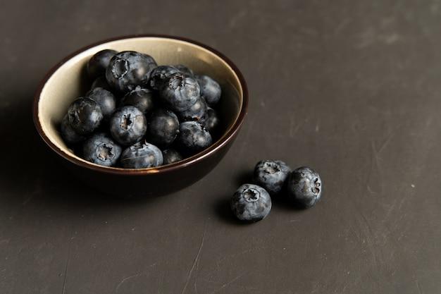 Blaubeerantioxidansorganisches superfood in der keramischen schüssel für draufsicht der gesunden ernährung und der nährenden nahrung über dunkles schwarzes