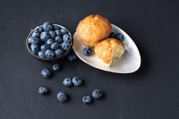 Blaubeerantioxidansorganisches superfood in der keramischen schüssel und im süßen muffin für draufsicht der gesunden ernährung und der diätnahrung über dunkles schwarzes