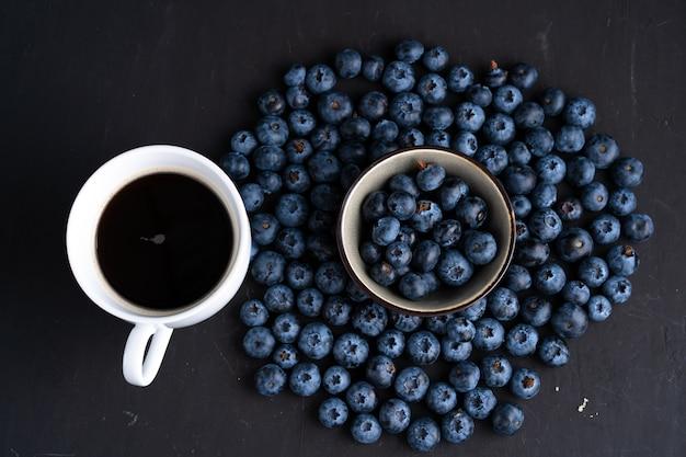 Blaubeerantioxidansorganisches superfood in der keramischen schüssel und im tasse kaffee für draufsicht der gesunden ernährung und der nährenden nahrung über dunkles schwarzes