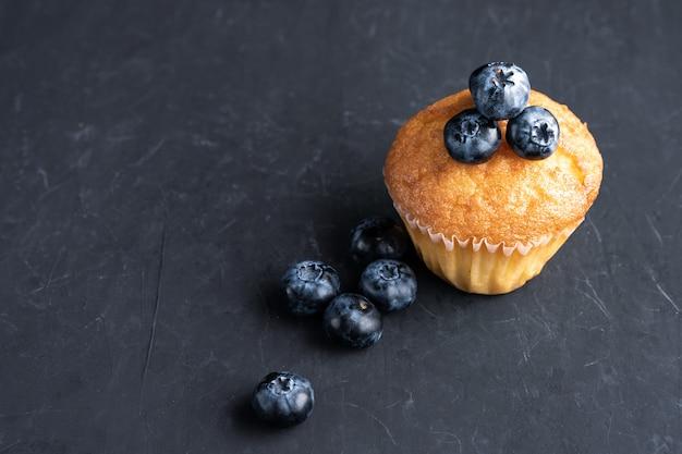 Blaubeerantioxidansorganisches superfood und süßes muffin für draufsicht der gesunden ernährung und der nährenden nahrung über dunkles schwarzes