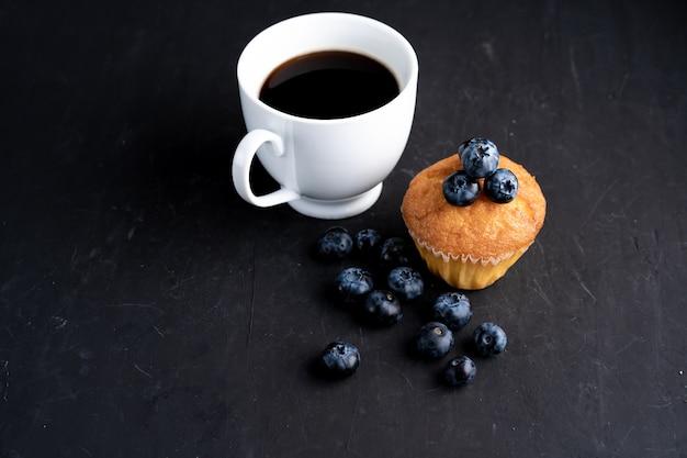 Blaubeerantioxidansorganisches superfood und süßes muffin mit tasse kaffee für draufsicht der gesunden ernährung und der nährenden nahrung über dunkles schwarzes
