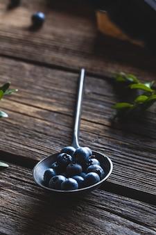 Blaubeere im löffel auf hölzernem tischhintergrund. blaubeeren schließen. gesundes essen, gesundheit