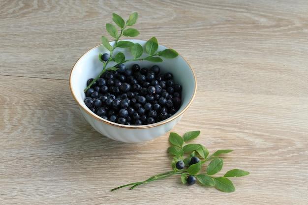 Blaubeere in der keramischen schüssel lokalisiert auf weiß. frische blaubeernahaufnahme, ernährungskonzept der gesunden ernährung. reife bio-heidelbeere, vegane mahlzeit. saftiger blaubeerhintergrund.