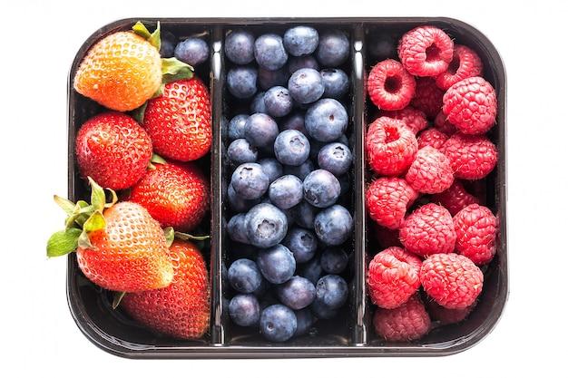 Blaubeeren, erdbeeren und himbeeren in einem kasten lokalisierten o