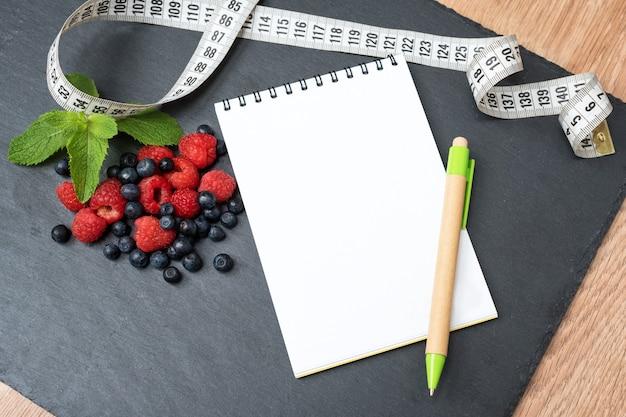 Blaubeeren, himbeeren, minze, maßband und notizblock zum schreiben von notizen