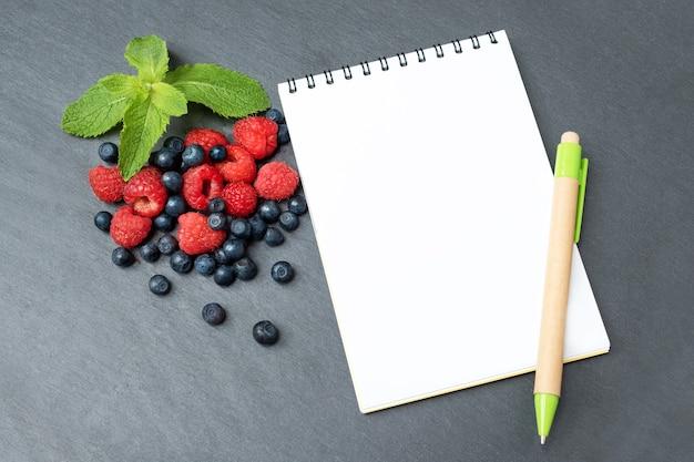 Blaubeeren, himbeeren, minze und notizblock zum schreiben von notizen
