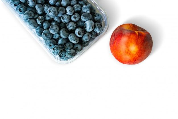 Blaubeeren im behälter und in pfirsich lokalisiert