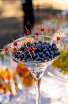Blaubeeren im glas. hölzerne pi?ks in beeren. catering zur hochzeit. hochzeitsbanketttisch. süßer tisch mit obst, hochzeitscatering. fruchtbar auf party.