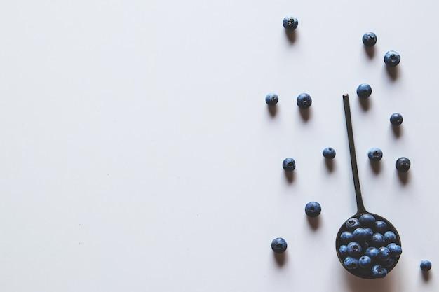 Blaubeeren in einem löffel lokalisiert auf einem weißen hintergrund. weißer hintergrund mit blaubeeren. blaubeer-randdesign. draufsicht oder flache lage. gesundes essen, gesundheit