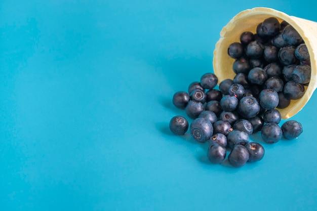 Blaubeeren in einem waffel-eisbecher auf hellblauem hintergrund. supervitamin blaubeere. vegetarisches eis