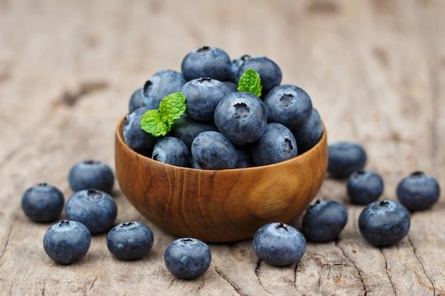 Blaubeeren in einer hölzernen schüssel auf einem holztisch, einer gesunden ernährung und einem nahrungskonzept