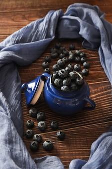 Blaubeeren in einer teekanne auf holztisch