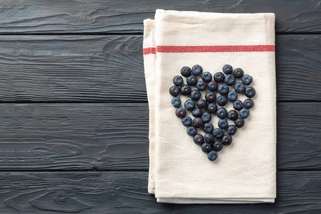 Blaubeeren in herzform auf küchenserviette auf holztisch gebildet