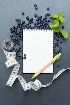Blaubeeren, minzblätter und notizblock zum schreiben von notizen