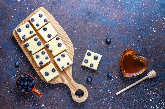Blaubeerkäsekuchenriegel mit honig und frischen beeren