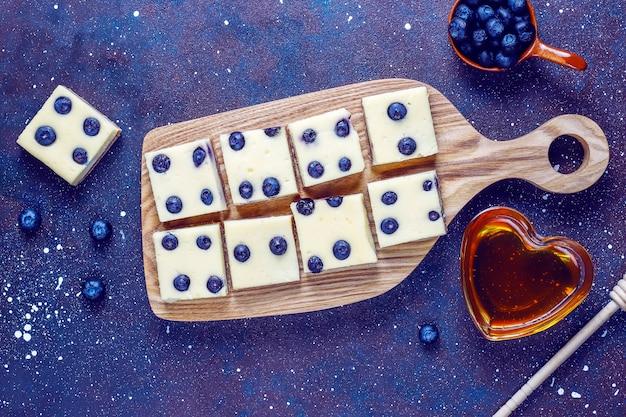 Blaubeerkäsekuchenriegel mit honig und frischen beeren.