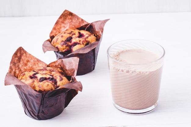 Blaubeermuffin in braunem papier und glas mit leckerer schokoladenmilch auf weißem hintergrund, hausgemachtes backen.